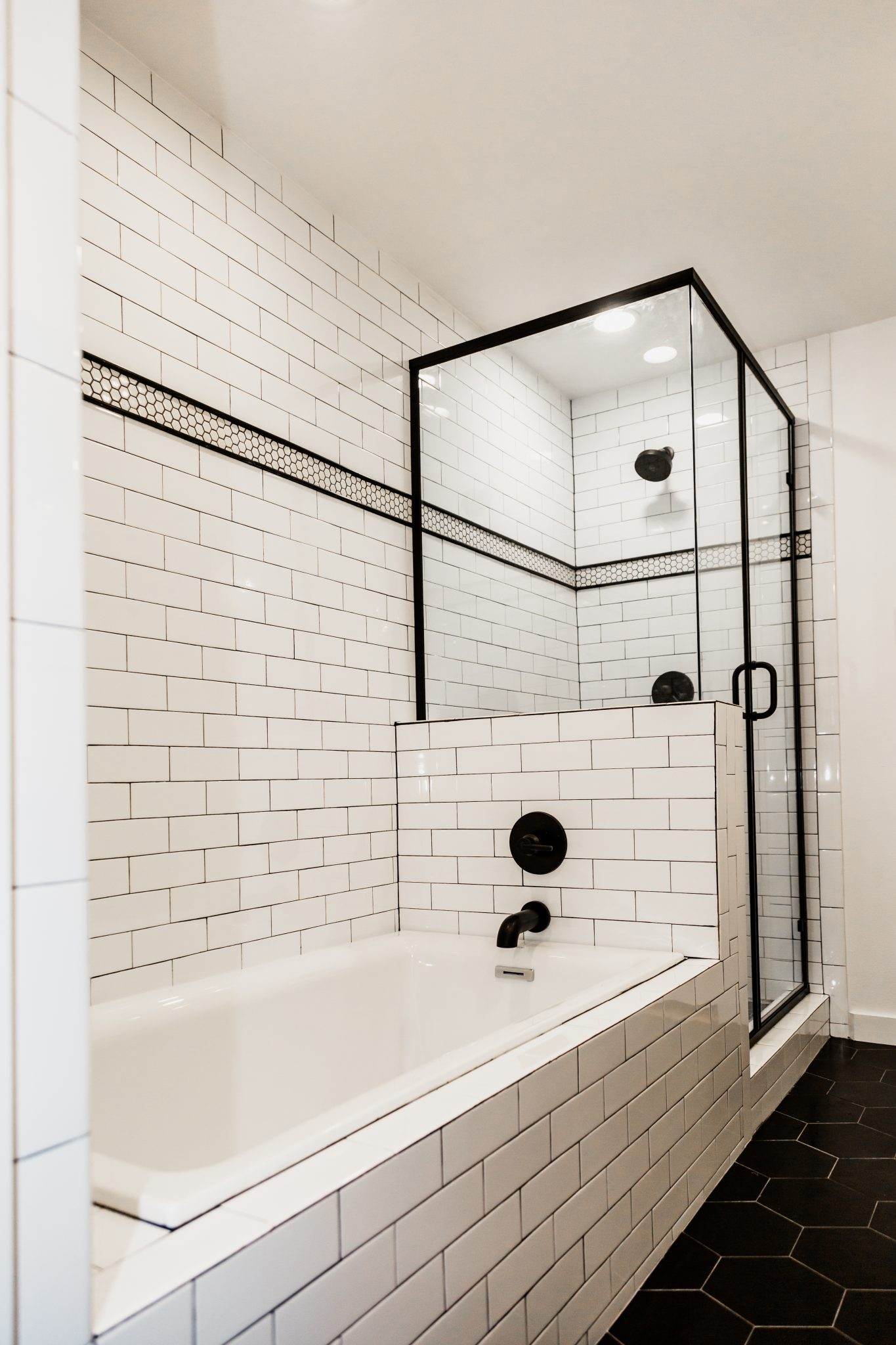 Black frame shower, drop in bathtub with subway tiles, Matte black fixtures, subway tile wall surround, Shower and bathtub connected
